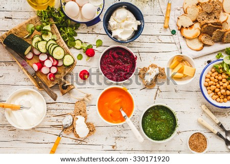 Dinner food table. Creamy pumpkin, beetroot, spinach soup with chickpeas dish - homemade recipe of cream vegetarian dish with vegetables and bread slices on a wooden table. Rustic style. - stock photo