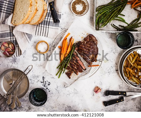 Dinner food tabletop. Overhead of Bbq fillet steak sliced with potatoes, carrot, green beans fries on a grey table. Top view.  - stock photo