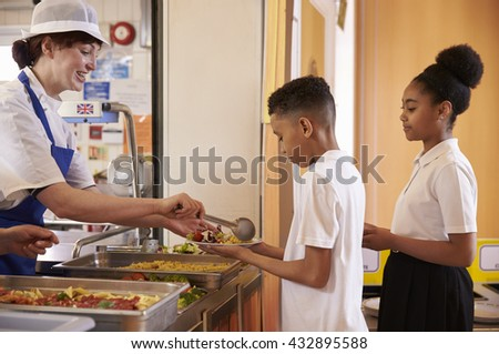 Dinner lady serving kids in a school cafeteria, side view - stock photo