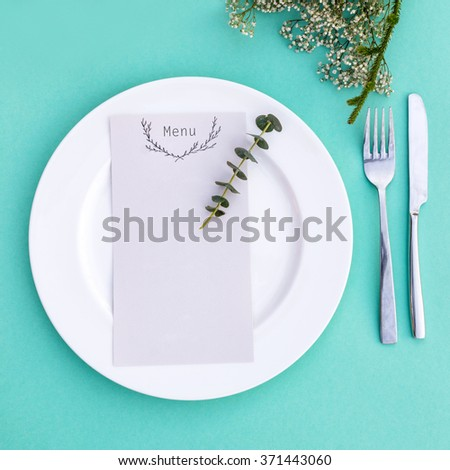 Dinner menu for a wedding or luxury evening meal. Table setting from above. Elegant empty plate, cutlery and flowers - stock photo