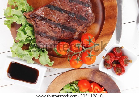 dinner of fresh rich juicy grilled beef meat steak fillet with marks on wooden plate over white table served with vegetable salad and cutlery, new york styled cuisine - stock photo