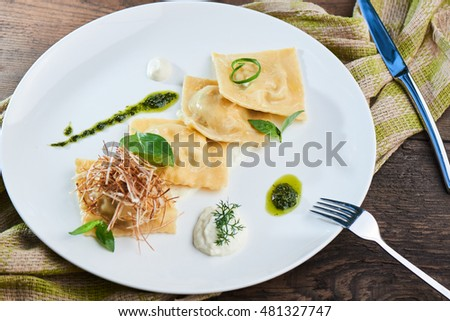 Dinner of ravioli with duck and cream sauce, served on a white plate