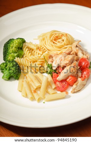 Dinner of vegetables pasta tomato and chicken on a white plate and wooden table