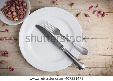 Dinner place setting - plate of white porcelain, fork, and knife on white, old, wooden table - stock photo