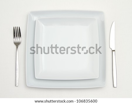 Dinner place setting. white square china plates with silver fork and knife - stock photo