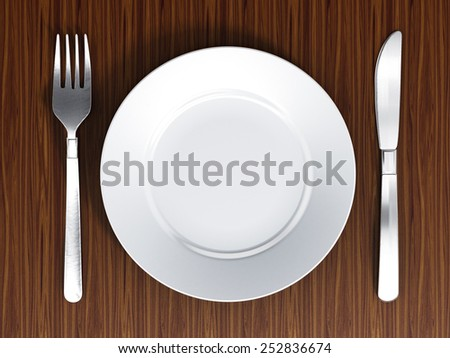 Dinner plate, fork and knife on wood surface