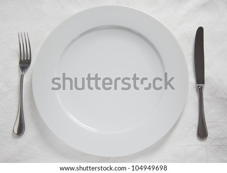 Dinner Plate, Knife and Fork on linnen cloth - stock photo