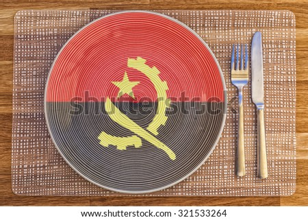 Dinner plate with the flag of Angola on it for your international food and drink concepts. - stock photo