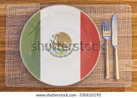 Dinner plate with the flag of Mexico on it for your international food and drink concepts. - stock photo