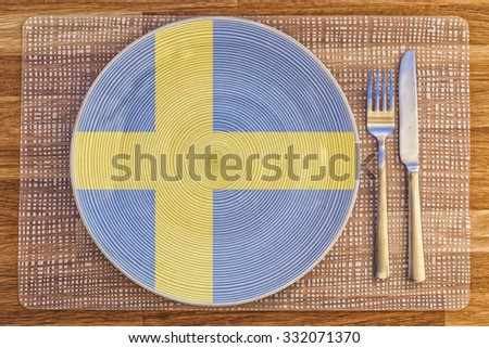 Dinner plate with the flag of Sweden on it for your international food and drink concepts. - stock photo