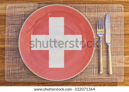 Dinner plate with the flag of Switzerland on it for your international food and drink concepts. - stock photo