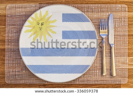Dinner plate with the flag of Uruguay on it for your international food and drink concepts. - stock photo