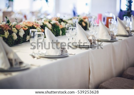 Dinner plates with serviettes and little present boxes stand on the table