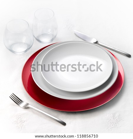 Dinner set on white tablecloth - stock photo