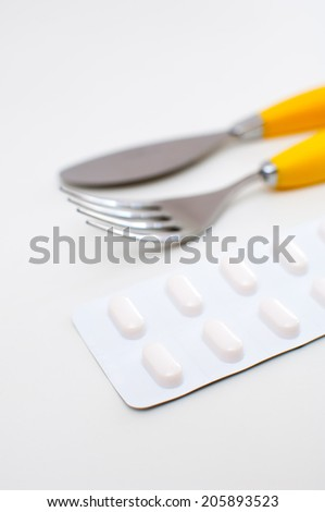 Dinner set with pills on white background.