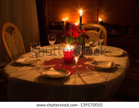Dinner table at candlelight with flowers, glasses and plates - stock photo