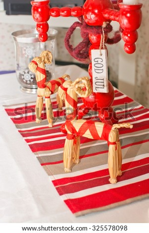 Dinner table rustic Christmas setting with straw goats and wooden candle holder in traditional colors red and white, with the words 'God Jul' meaning 'Merry Christmas', Sweden.  - stock photo