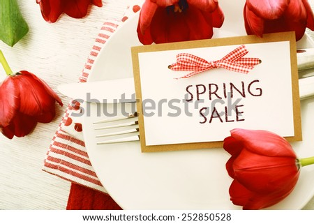 Dinner table setting with Spring Sale message card and red tulips - stock photo