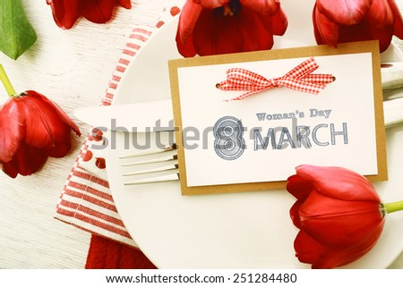 Dinner table setting with Woman's day message card and red tulips - stock photo