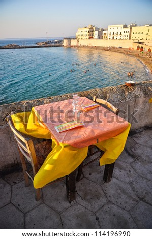 Dinner table with view on the Gallipoli's beach at sunset, holiday destination in Apulia, Italy. - stock photo
