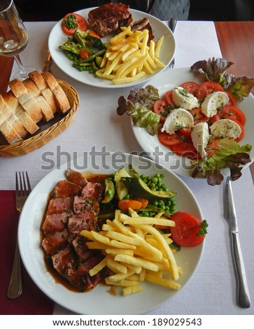 Dinner tables with grilled beefsteak, french fries and vegetables