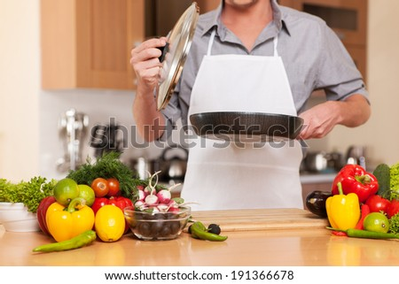 Dinner time. Man cooking in the kitchen - stock photo
