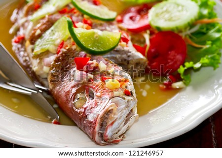 Dinner with freshly prepared Thai style whole red snapper fish