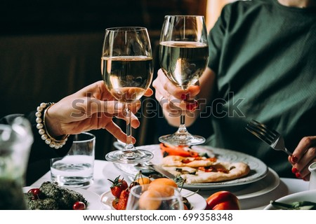 Dinner with friends of family served in a restaurant. Two glasses of white wine in hands