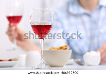 Dinner with glasses of wine on light blurred background