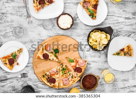 dinner with pieces of pizza on board and plates top view - stock photo