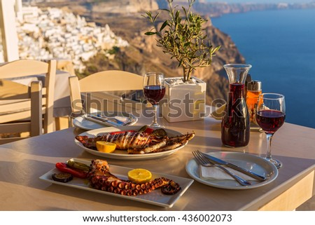 Dinner with seafood and red wine on the background of sea sunset