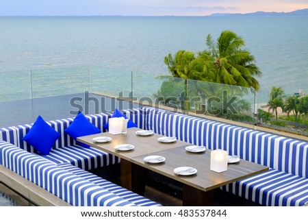 dinning table and sofa at rooftop of hotel beside sea