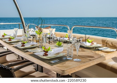 Dinning table on the upper deck in luxurious yacht. - stock photo