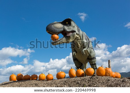 dinosaur holding pumpkin in mouth outdoors - stock photo