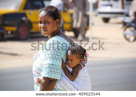 DIOURBEL/SENEGAL - NOVEMBER 15, 2013: Little african girl hanging and cuddling at the mother's back - stock photo