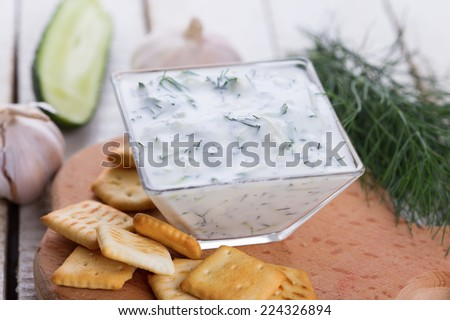 Dip sauce tzatziki with fresh yogurt, cucumber, garlic, herbs in bowl and crackers on wooden background. Selective focus, horizontal. - stock photo