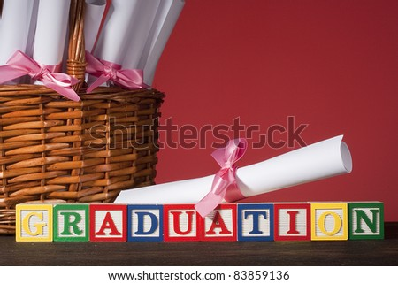 """Diploma tied with a ribbon, the text of the wooden blocks """"Graduation"""". - stock photo"""