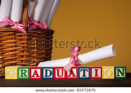"""Diploma tied with a ribbon, the text of the wooden blocks """"Graduation'. - stock photo"""