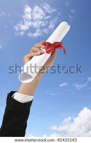 Diploma with a red ribbon in hand on sky - stock photo