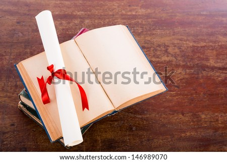 Diploma with old book - stock photo