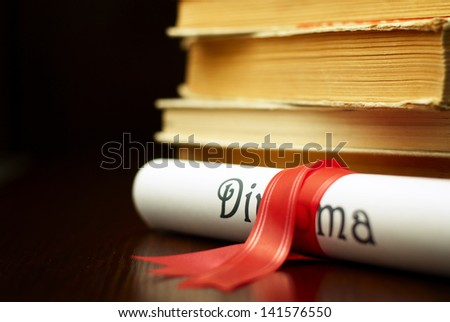 Diploma with red ribbon and a stack of books - stock photo