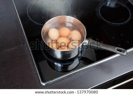 dipper of water on the kitchen stove - stock photo