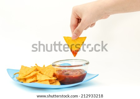 Dipping tortilla chips with salsa sauce in dish on isolated white background - stock photo