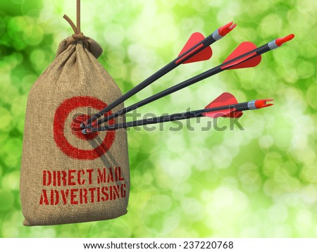 Direct Mail Advertising - Three Arrows Hit in Red Target on a Hanging Sack on Natural Bokeh Background. - stock photo