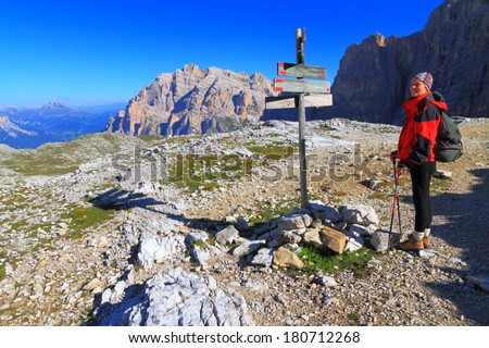 Direction indicator and tourist searching the route, Dolomite Alps, Italy - stock photo
