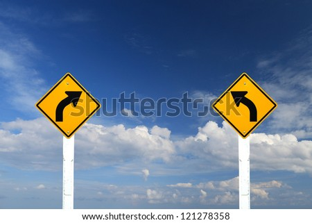Direction sign- left and right turn warning on blue sky background with blank for text - stock photo