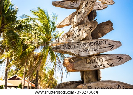 Direction signs to various cities, funny stand on the beach - stock photo