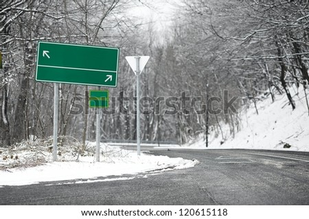 Direction sing on a road in winter - stock photo