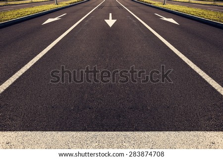 Directional arrows on the asphalt road. Toned photo. - stock photo