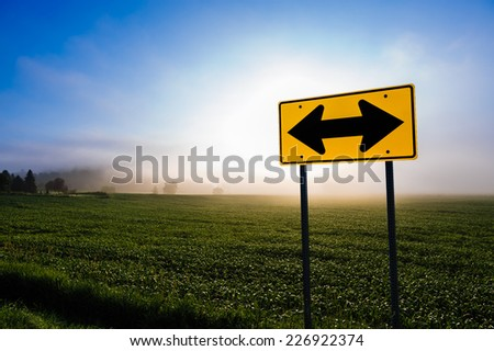 Directional road sign in front of a corn field, Stowe, Vermont, USA. - stock photo